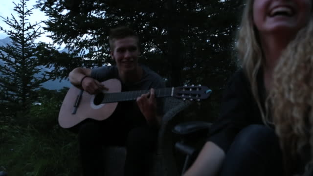 Pan up to young girl roasting marshmellows on a campfire as a young man plays the guitar