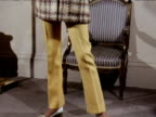 Pan up woman modeling trousers coat and hat 1970