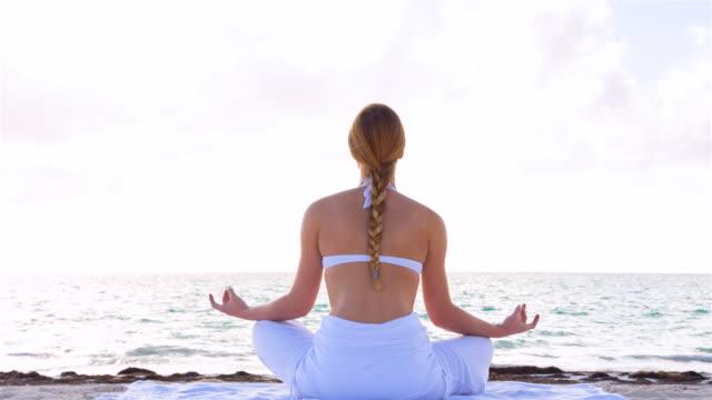 MS pan up, young woman doing yoga at tropical beach