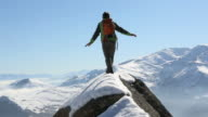 Pan upwards to climber balancing on narrow ridge crest