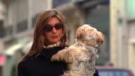 Pan woman walking on street carrying small dog / she raises hand to block camera / Paris, France