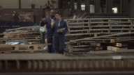 WS PAN_Coworkers walking and talking at steel plant, holding digital tablet