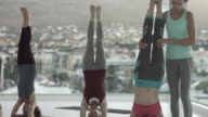 MS PAN_Yoga teacher instructing students in handstand, in rooftop studio