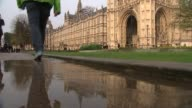 David Cameron faces MPs amid tax affairs row EXT Reflection of Big Ben clock tower in puddle of water Legs along through puddle opposite Houses of...