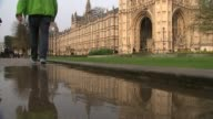 David Cameron faces MPs amid tax affairs row EXT Reflection of Big Ben in puddle of water Legs along through puddle opposite Houses of Parliament...