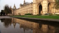 David Cameron faces MPs amid tax affairs row House of Parliament People along through puddles on pavement Reflection of Big Ben clock tower in puddle...