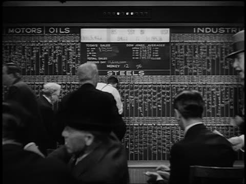 B/W 1929 REENACTMENT REAR VIEW panicked stockbrokers watching stock price board + ticker