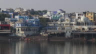 Panning across the architecture and buildings of temples and the ghats at the holy Lake of Pushkar in Pushkar town, Rajasthan, India
