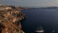 Panning across the bay to the white washed houses of Thira overlooking the Aegean Sea on the Island of Santorini, Greece, Europe