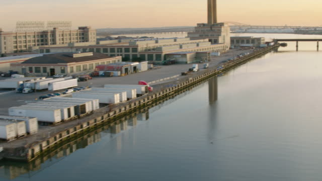 Panning aerial of parking lot with trucks parked, over river to industrial area