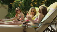 Panning medium shot of girls in bathing suits eating watermelon at poolside / Cedar Hills, Utah, United States