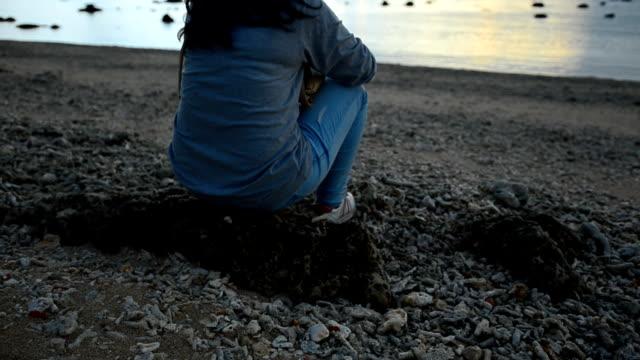 panning: Sad unhappy girl sitting on beach in sunset