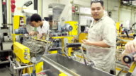 panning: senior teach two young engineer operate twin screw  extruder