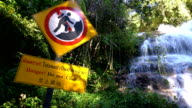 Panning shot 4K, warning sign at Mon Tha Than waterfall.