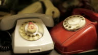 Panning shot across a shelf of old telephones.
