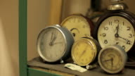 Panning shot across old clocks on a shelf.
