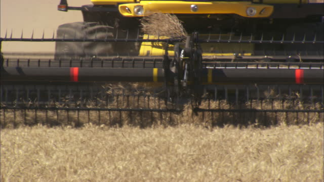 Panning shot across the spinning blades of a combine harvester.