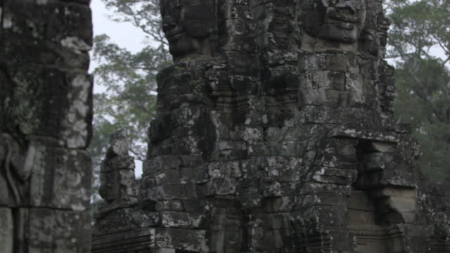 Panning shot across the stone faces decorating the exterior of the Bayon temple at Angkor.
