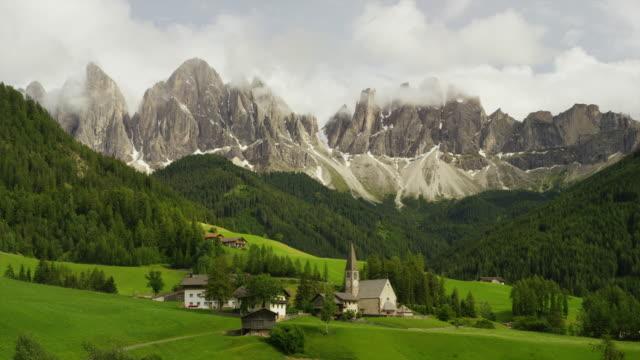 Panning shot church nestled in rolling landscape under mountains / Santa Magdalena, Dolomites, Italy