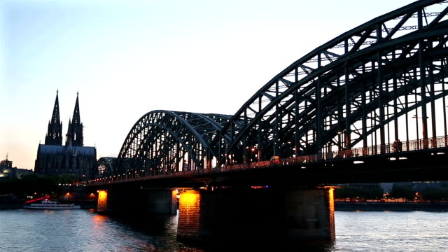 Panning shot: Cologne Cathedral and Hohenzollern Bridge at dusk Germany