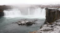 Panning shot: Iceland Godafosss Waterfall in winter with snow