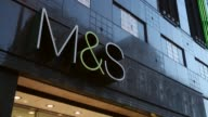 Panning Shot Marks and Spencer logo Members of the public walk past a branch of Marks Spencer on Oxford Street on January 7 2014 in London England...