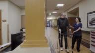 Panning shot of a senior man using a walker