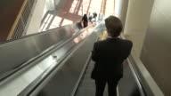 Panning shot of business people using an escalator