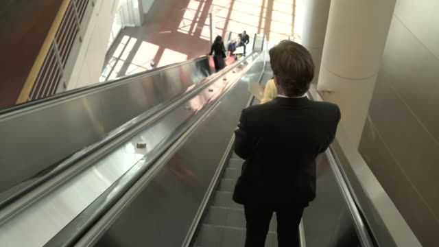 Panning shot of business people using an escalator