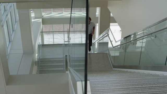 Panning shot of businessman running up staircase in office / Provo, Utah, United States,