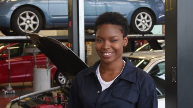Schuss der fröhliche junge Frau in der Schule lernen Mechaniker schwenken