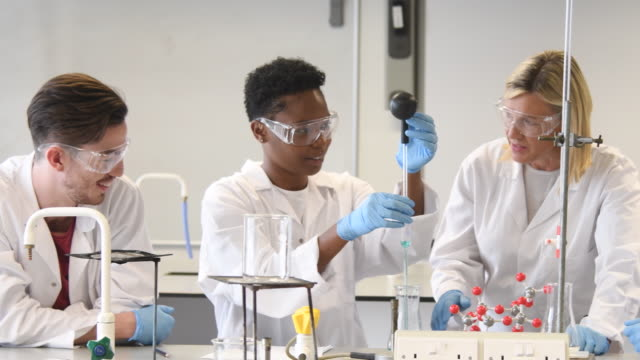 Panning shot of college students working in laboratory with teacher