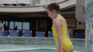 Panning shot of girl jumping into swimming pool / Gulf Of Mexico, Mexico,