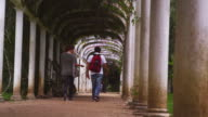 Panning shot of male and female walking under arches.