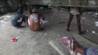 Panning Shot of male crack users to female lying on a mattress Crack Land in the suburbs of Rio de Janeiro shot on December 10 2013