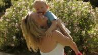 Panning shot of mother and toddler playing/Benhavis, Marbella region, Spain