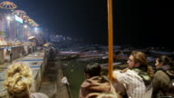 Panning shot of several non Indian people watching a incense offering in an Indian town.