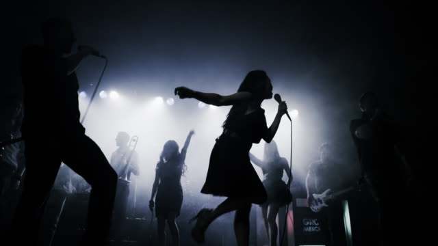 Panning shot of silhouetted singers and musicians performing on stage / Spanish Fork, Utah, United States,