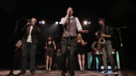 Panning shot of singers and musicians performing on stage / Spanish Fork, Utah, United States,