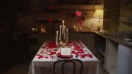 Panning shot of table covered in candles, rose petals and Valentine candy / Lehi, Utah, United States,