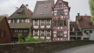 Panning shot of traditional houses and cobblestone bridge in village / Ulm, Germany