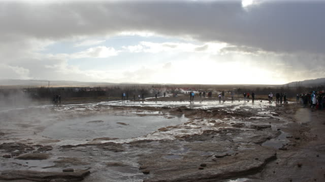 Panning shot: Tourist at Strokkur Geyser in Iceland