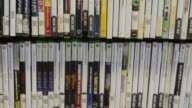 Panning shots of a rack of new and used XBOX 360 games for sale at Game Stop in Peru Illinois