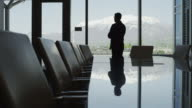 Panning silhouette of businessman standing in conference room / Provo, Utah, United States,