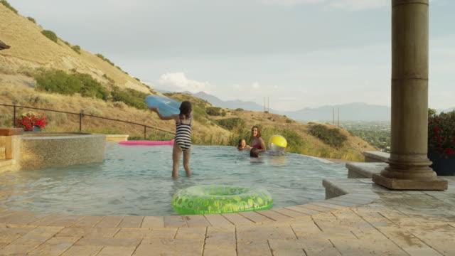 Panning time lapse medium shot of girls playing in swimming pool / Cedar Hills, Utah, United States