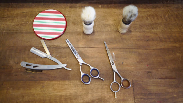 Panning view of a barbers tools on a wooden table
