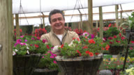 Panning view of a gardener at a garden center