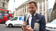 Panning view of business man texting on his phone outside