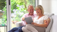Panning view of couple looking at something on tablet and laughing