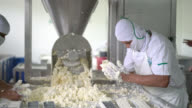 Panning view of men working at a dairy factory making cheese